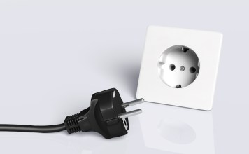 european disconnected black plug lies on the ground in front of a white socket