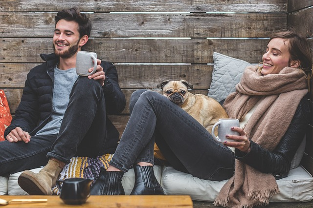 A young couple drinking coffee with dog in lap.