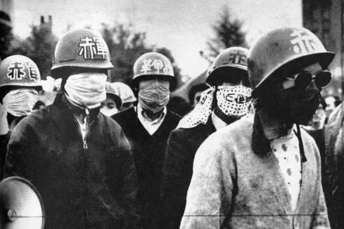 Estudiantes japoneses protestando con cascos y palos.