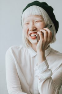 a woman smiling while on a phone call