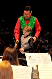 Lakeland Concert Band conductor, Vic Larsen, assists a young conductor