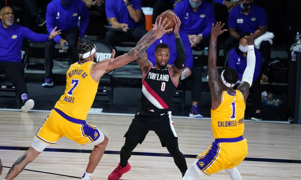 Portland Trail Blazers guard Damian Lillard (0) tries to pass under pressure from Los Angeles Lakers center JaVale McGee (7) and guard Kentavious Caldwell-Pope (1) during the second half of an NBA basketball game Tuesday, Aug. 18, 2020, in Lake Buena Vista, Fla.