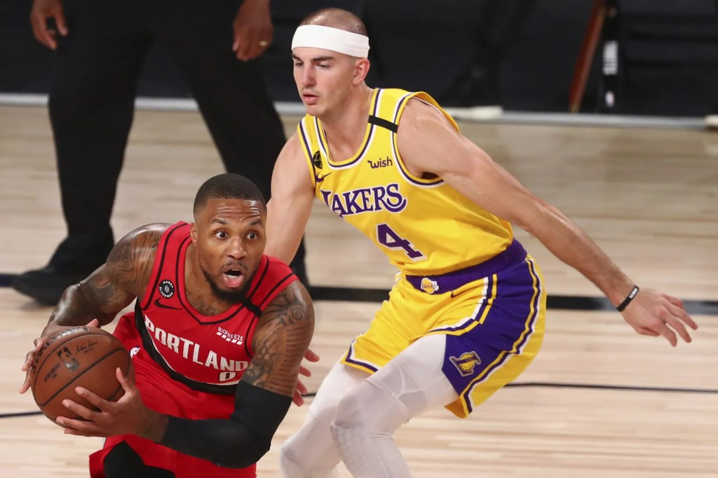 Portland Trail Blazers guard Damian Lillard (0) drives against Los Angeles Lakers guard Alex Caruso (4) during the first half in Game 2 of an NBA basketball first-round playoff series, Thursday, Aug. 20, 2020, in Lake Buena Vista, Fla.