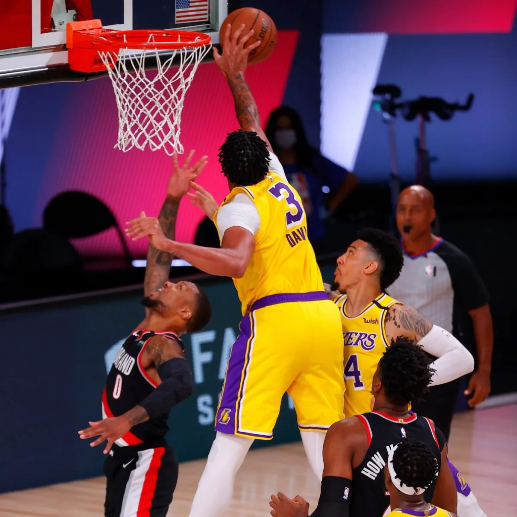 Anthony Davis #3 of the Los Angeles Lakers rebounds against Damian Lillard #0 of the Portland Trail Blazers during the third quarter in Game One of the Western Conference First Round during the 2020 NBA Playoffs on August 18, 2020