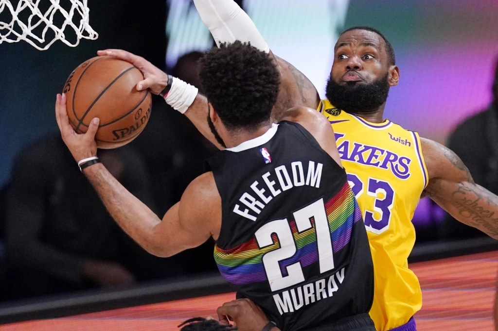 Denver Nuggets' Jamal Murray (27) drives against Los Angeles Lakers' LeBron James (23) and scores during the first half of an NBA conference final playoff basketball game Thursday, Sept. 24, 2020, in Lake Buena Vista, Fla.