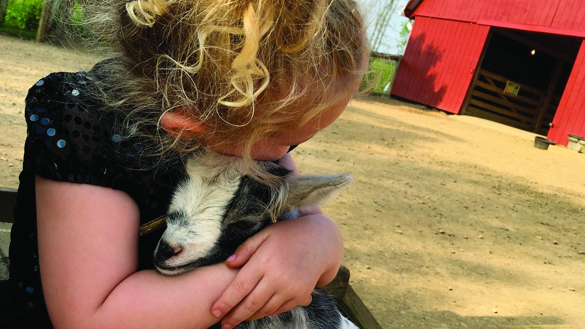 Girl hugging goat at Lake Tobias Wildlife Park