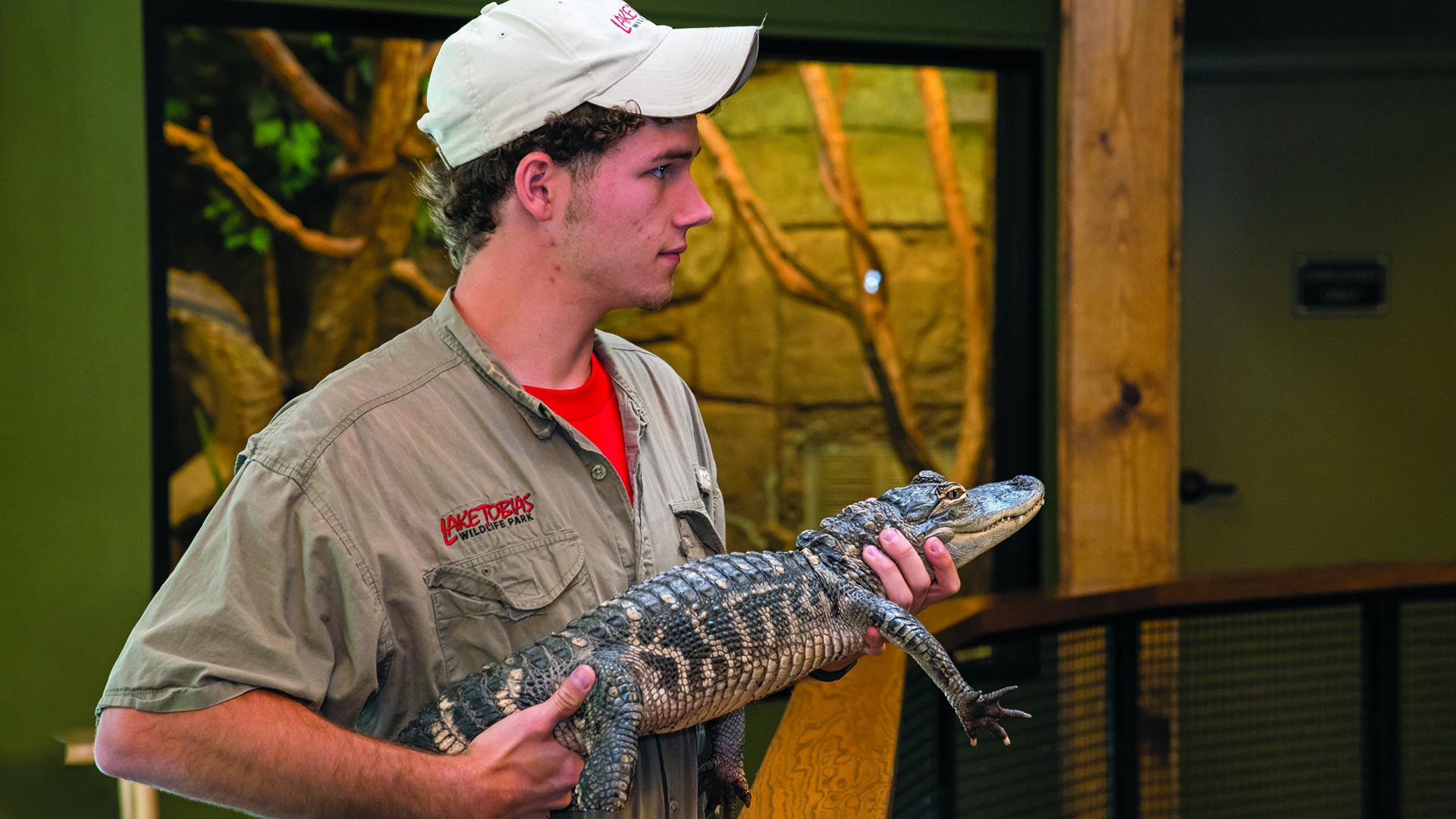 Park guide holding reptile at Lake Tobias Wildlife Park Reptiles & Exotics exhibit