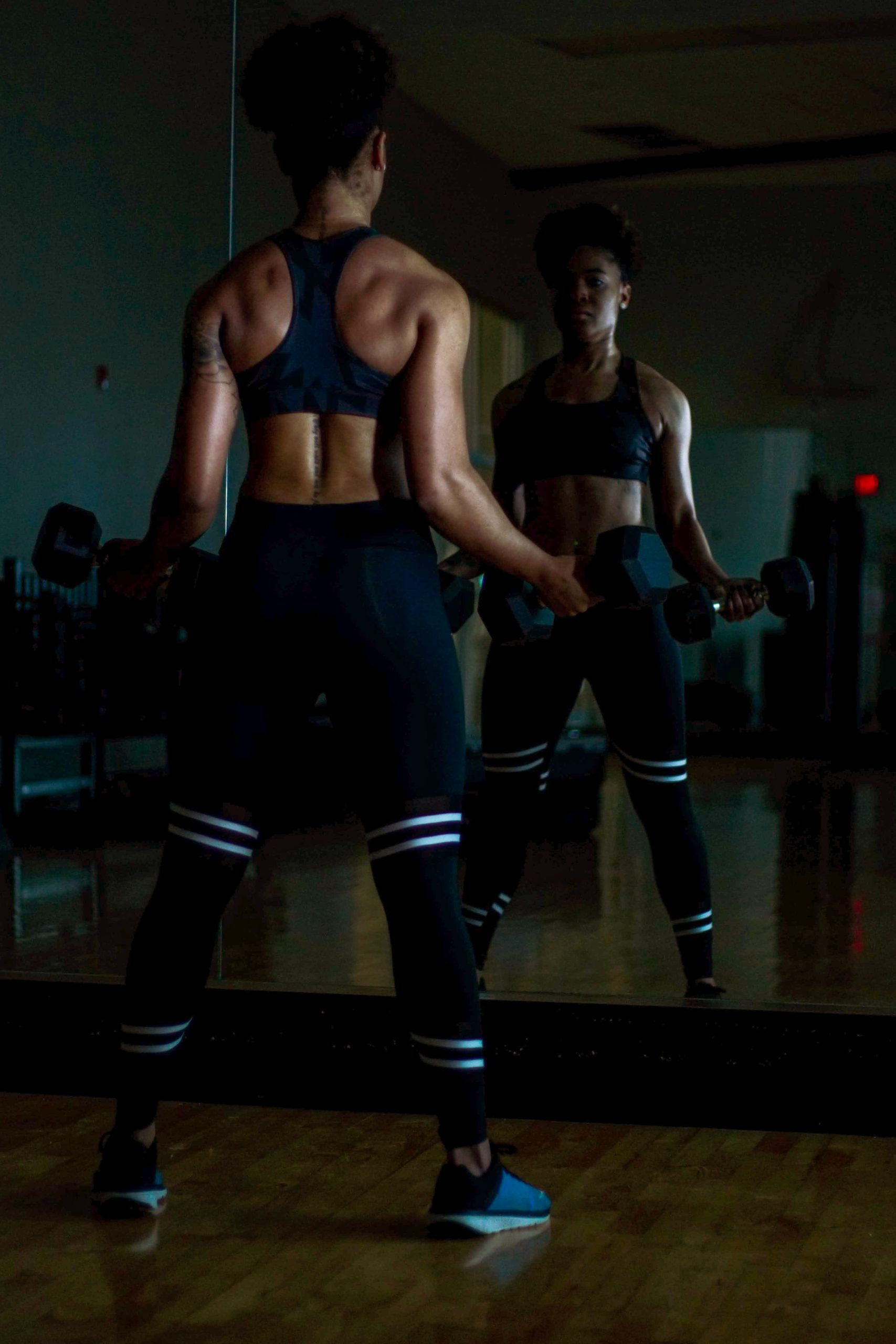 woman-lifting-two-dumbells-on-both-hands-in-front-of-mirror