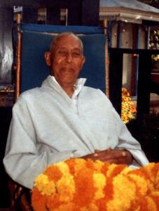 Swami Lakshmanjoo with orange flower leis