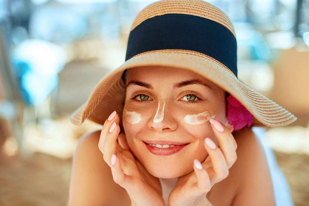 Soothing sunburn, Young pretty woman applying sun cream and touch own face.