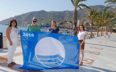 El director del Festival de Cine de l'Alfàs iza la Bandera Azul en la playa de l'Albir