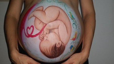 Pancia in gravidanza con sopra disegnato il bambino