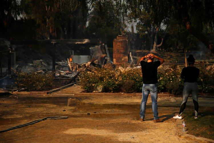 Alexander Tabolsky y Dina Arias observan la casa en la que vivían, hoy destruida
