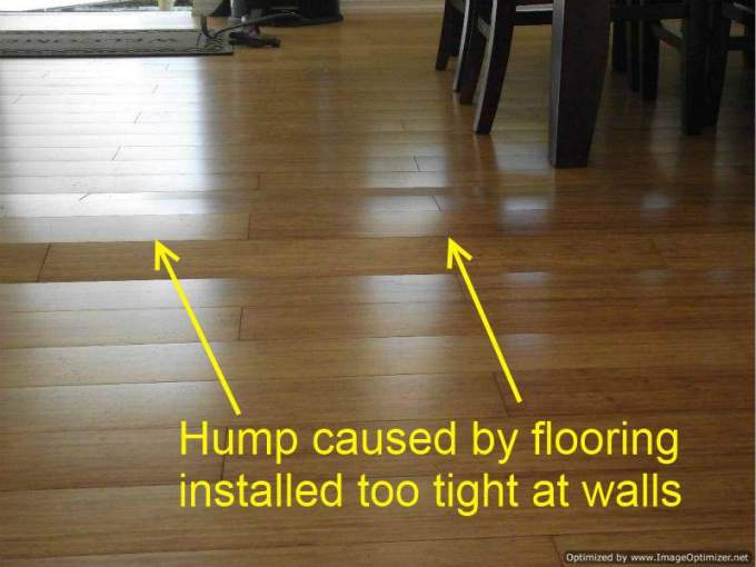 Bad Laminate Installation  Repair Hump on laminate flooring from being too tight against walls