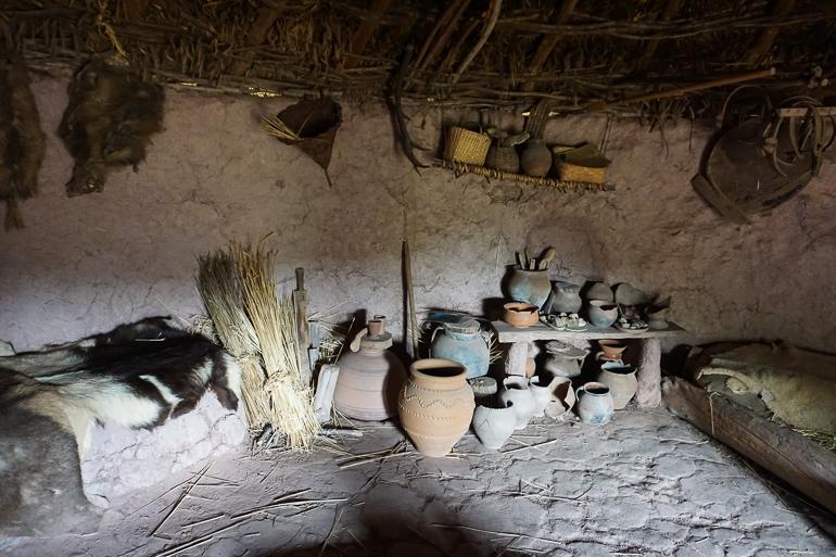 Interior de una de las casitas del poblado. Hay vasijas, paja, instrumentos para trabajar la tierra, cocinar.