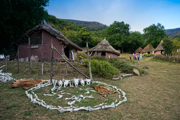 Casitas con tejados de paja y paredes de arcilla que emulan la forma de vida de los antiguos pobladores cántabros. En el primer plano se ve un círculo hecho con huesos de animales y calaveras de cabra.