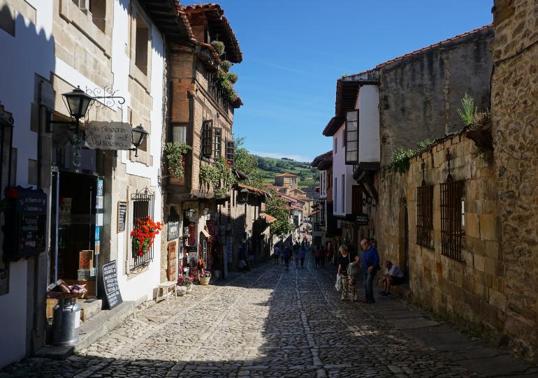 Calle empedrada y peatonal de Santillana del Mar. A los lados casitas bajas de piedra o con fachada blanca. Se ve gente paseando.