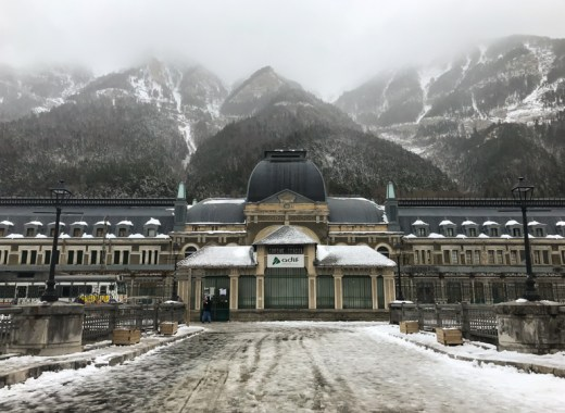 fachada principal de la estación de canfranc con las montañas nevadas al fondo