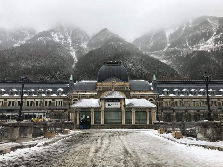 Fachada principal de la estación con las montañas nevadas al fondo