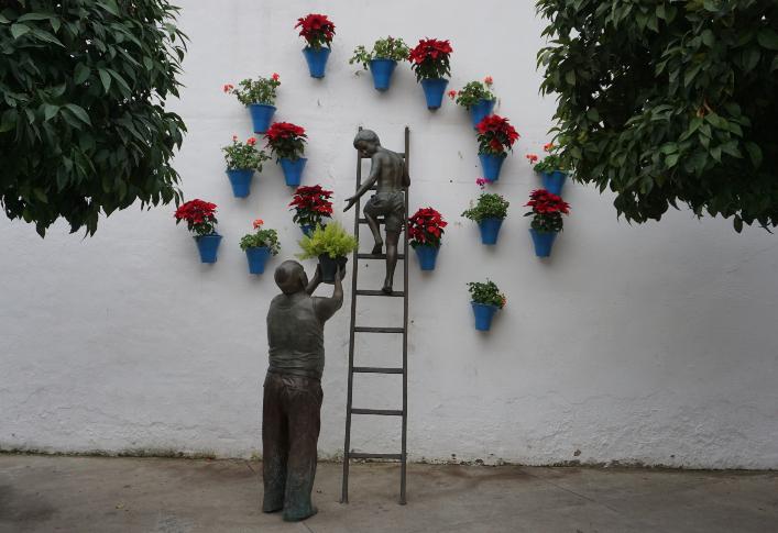 escultura de un hombre ayudando a un niño a cuidar las macetas del patio