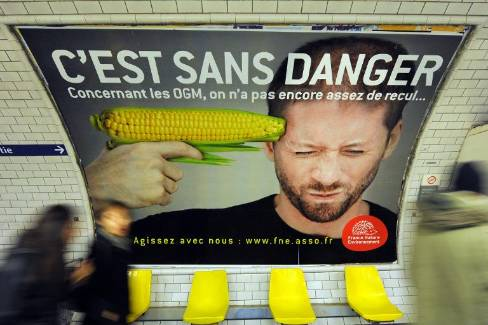 Des gens passent devant l'affiche d'une campagne contre les OGM menée par l'association France Nature Environnement, le 15 février 2011 dans le métro parisien - Miguel Medina/AFP