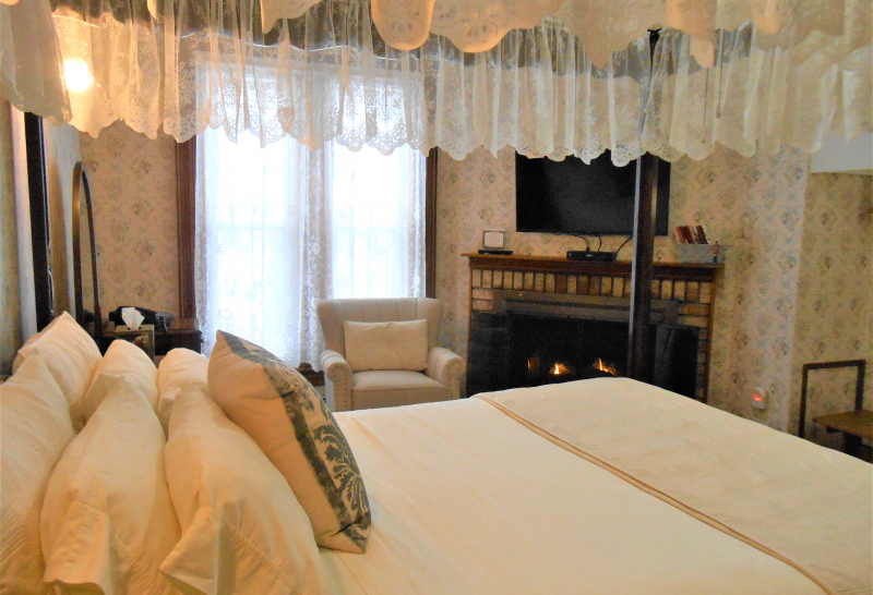 Guest room with canopy bed and fireplace