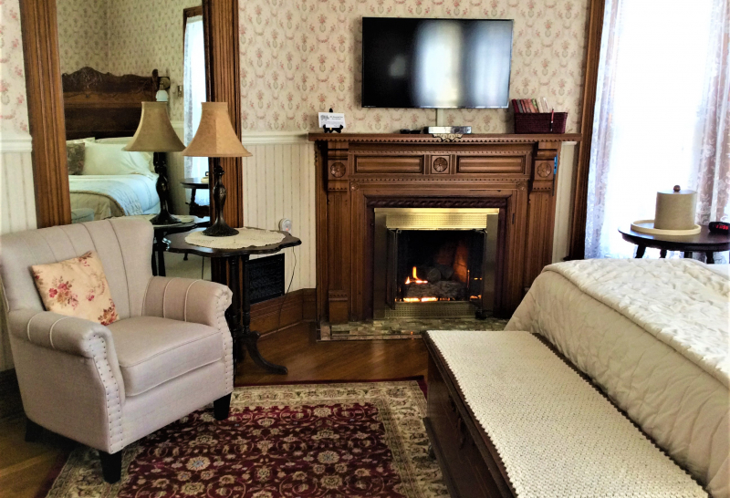 Fireplace in guest room with bed and chair