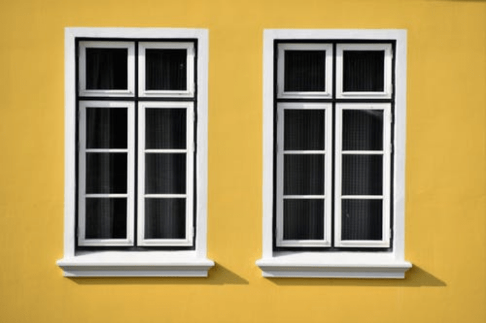 two windows on the yellow wall