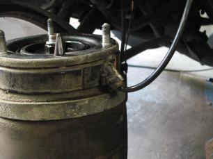 05- Maintenir l'ensemble amortisseur/ressort par le bas pour le désolidariser et dévisser complètement les 3 écrous du support moteur. Attention, l'ensemble amortisseur/ressort pèse près de 13 kg, il est donc préférable d'être deux. Dévisser ensuite l'écrou de raccordement de l'alimentation pneumatique.