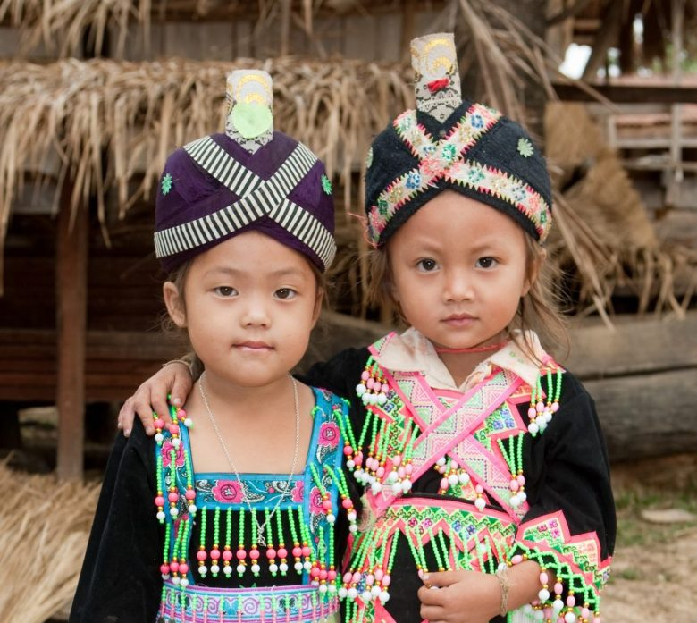 two little girls dressed in traditional Hmong-Lao garments