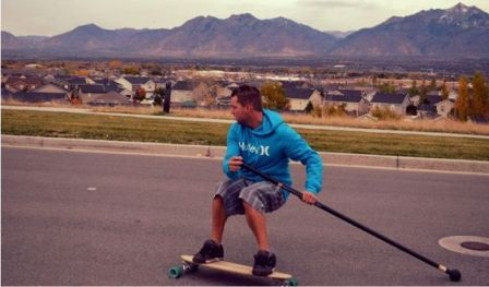 A skater land paddling down the street with a longboard land paddle.