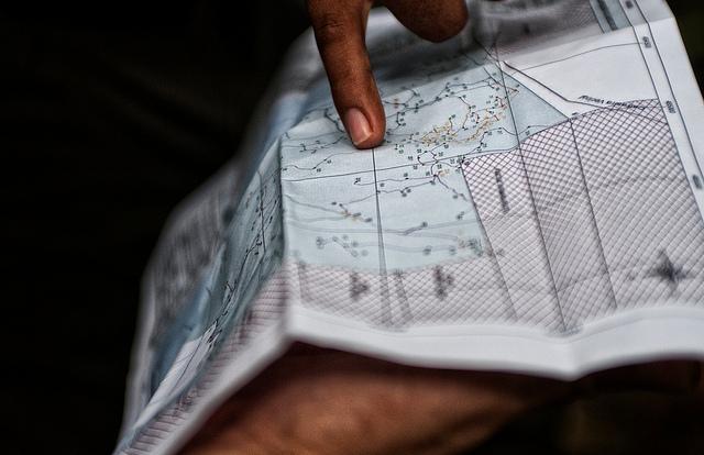 Center for International Forestry Reseach (CIFOR) scientists examining maps of Felicitas Ramirez Surco's Brazil nut concession, near Puerto Maldonado, Madre de Dios, Peru. Photo by Marco Simola for CIFOR)