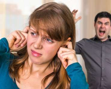 Couple arguing at home, angry man screaming at his wife