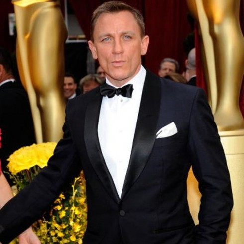 Actor Daniel Craig wears a black tuxedo, white shirt and white pocket square folded one corner up.