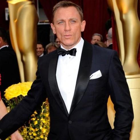 L'attore Daniel Craig indossa uno smoking nero, camicia bianca e pochette bianca ripiegata a punta.