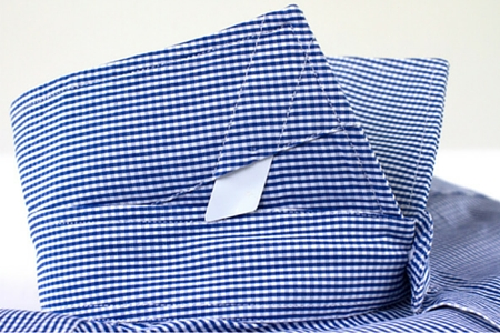 Close up on collar plastic removable white stays of a checkered dress shirt
