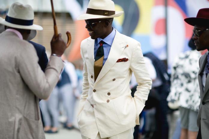 Uomo in abito avorio indossa un classico panama
