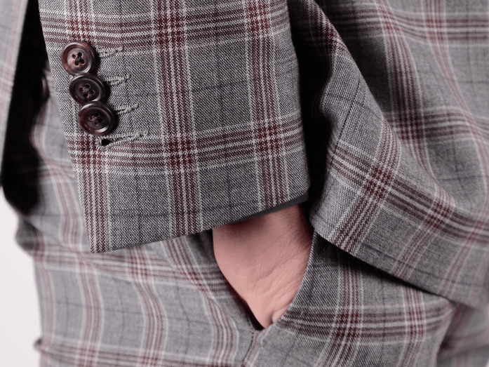 Detail on a 3 button jacket sleeve and hand in pocket