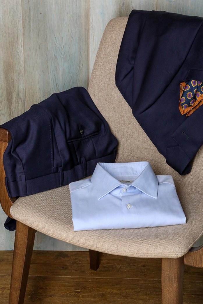 Camicia azzurra e completo blu appoggiati ad una sedia beige