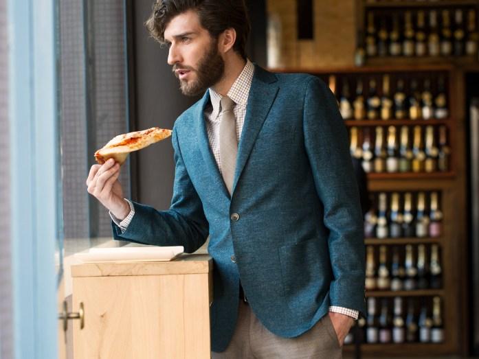 Un uomo indossa un blazer blu petrolio mentre regge una fetta di pizza