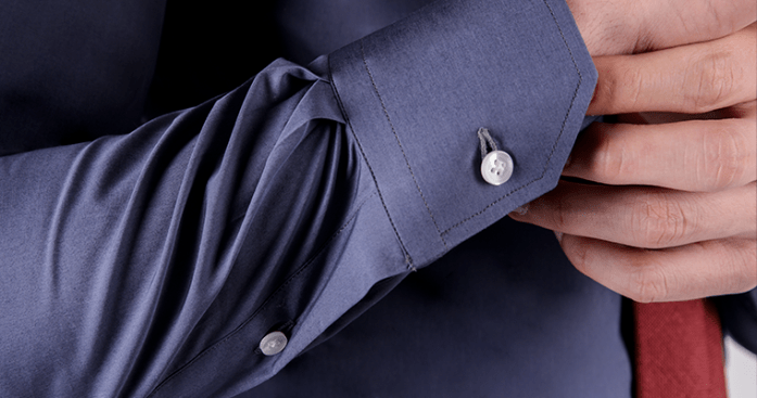 Close up on mitered cuff of a tailored cotton blue men's dress shirt