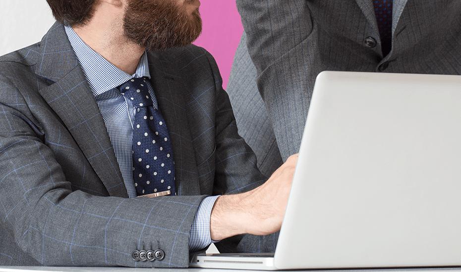 Uomini in abito scelgono giacca su misura per ufficio