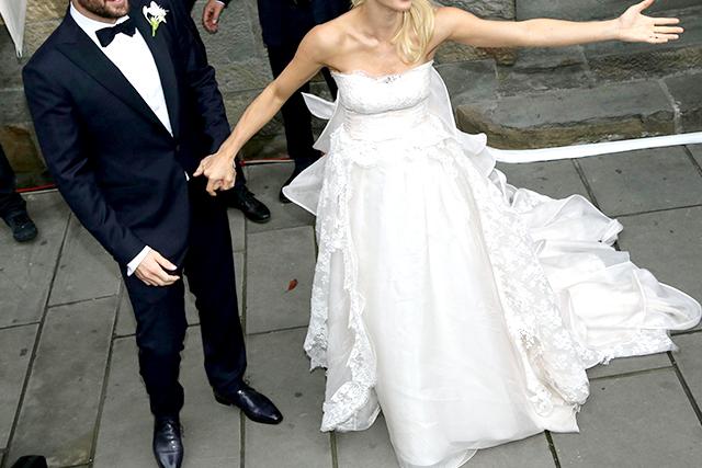 A man wears a blue groomed tuxedo, accompanied by a woman in a white wedding dress