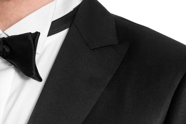 Dettaglio sui revers a lancia di uno smoking, indossato con papillon nero e camicia con collo diplomatico con alette