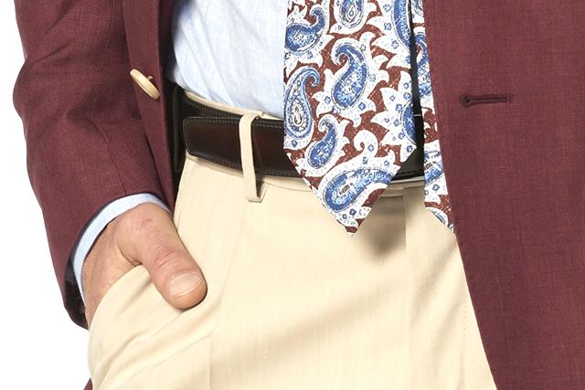 Particolare su uomo che indossa blazer bordeaux, camicia azzurra, cravatta paisley bordeaux e pantaloni chino beige di Lanieri