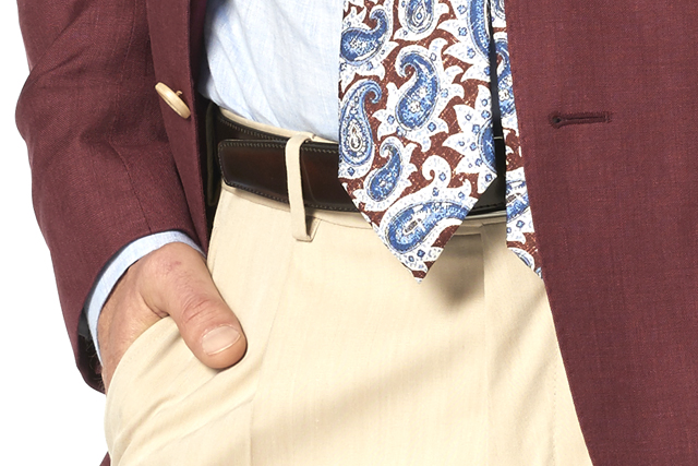 Detail on man wearing burgundy blazer, light blue shirt, burgundy paisley tie and beige chinos by Lanieri