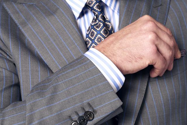 Uomo indossa abito grigio a righe azzurre realizzato da Lanieri, camicia bianca e a righe azzurre e cravatta murano blu