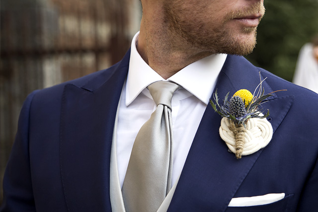 Man wears silver silk tie with blue tailored suit for ceremony