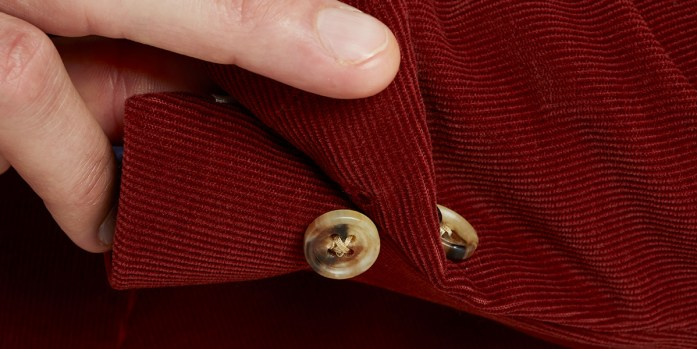 Button sleeve detail of a red corduroy blazer