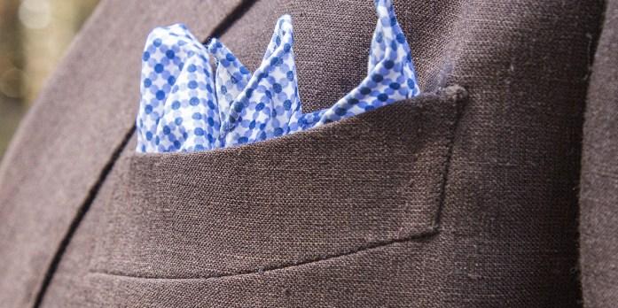 Pochette fantasia blu e bianca indossata su abito grigio